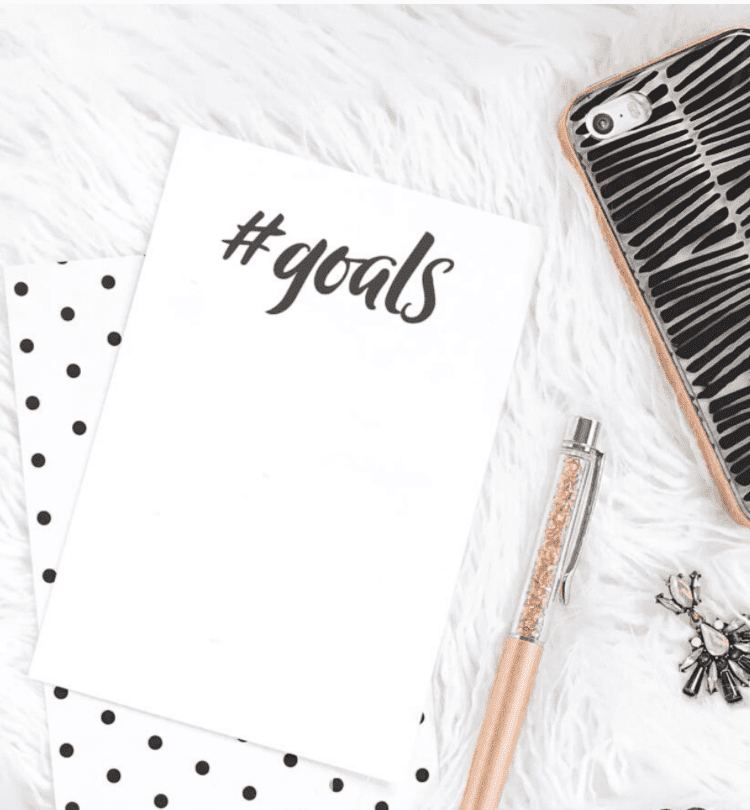Goals notepad on marble desk with a gold pen