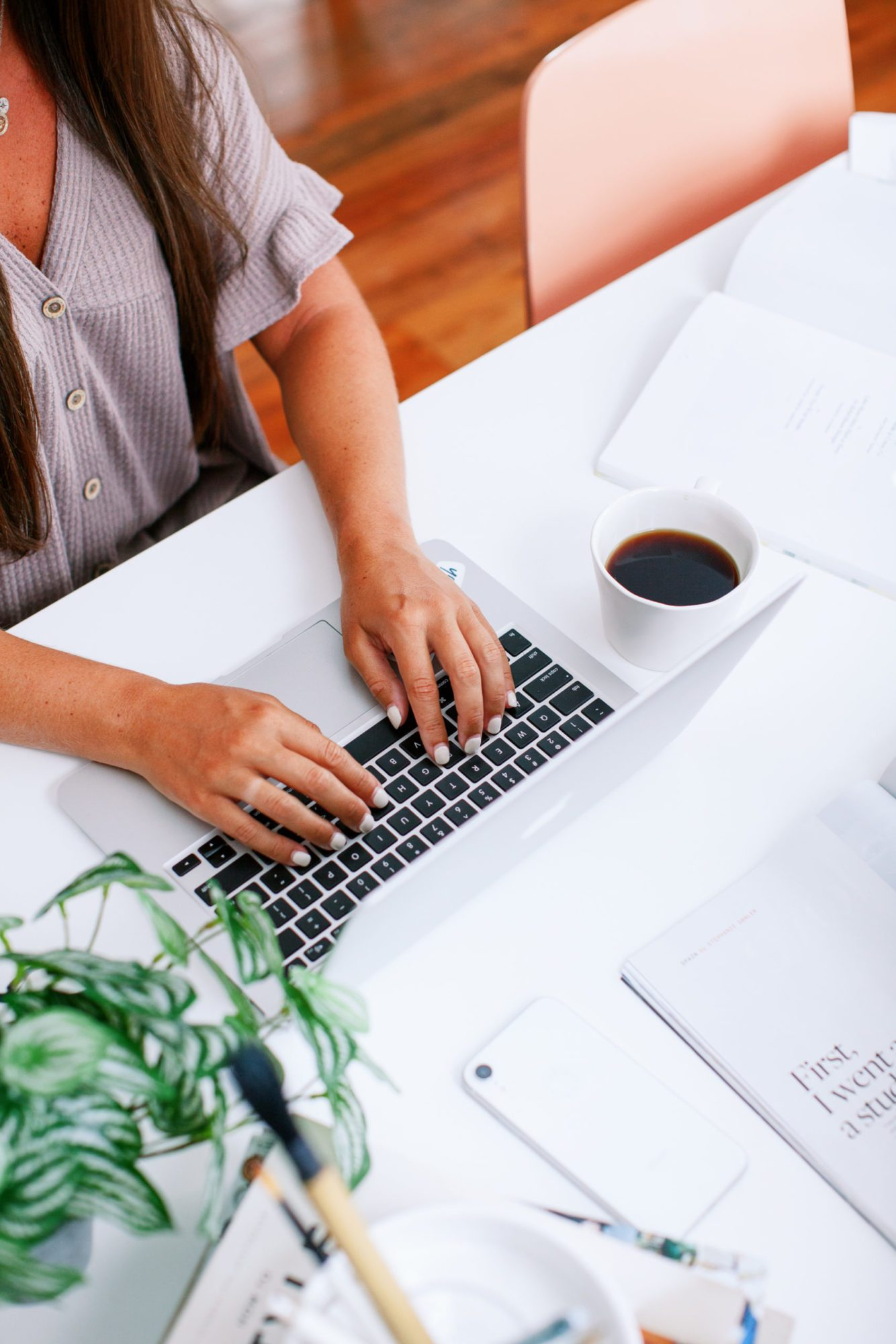 Woman typing on laptop with a cup of coffee