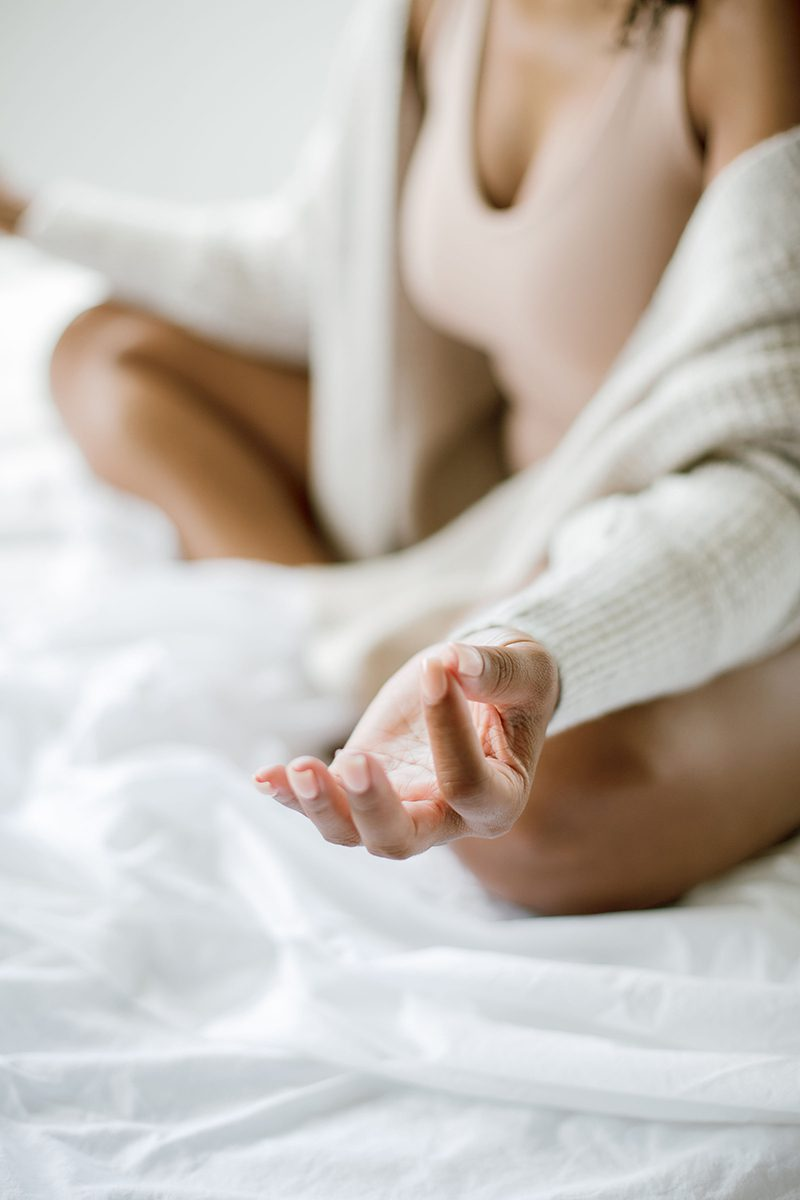Woman meditating on the bed