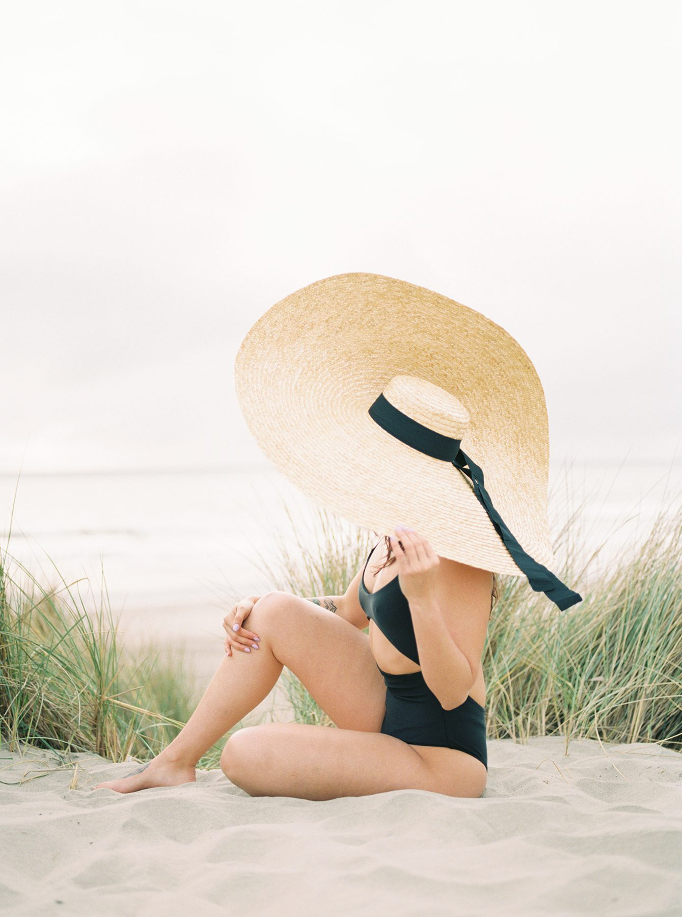 Woman in hat looking out at beach