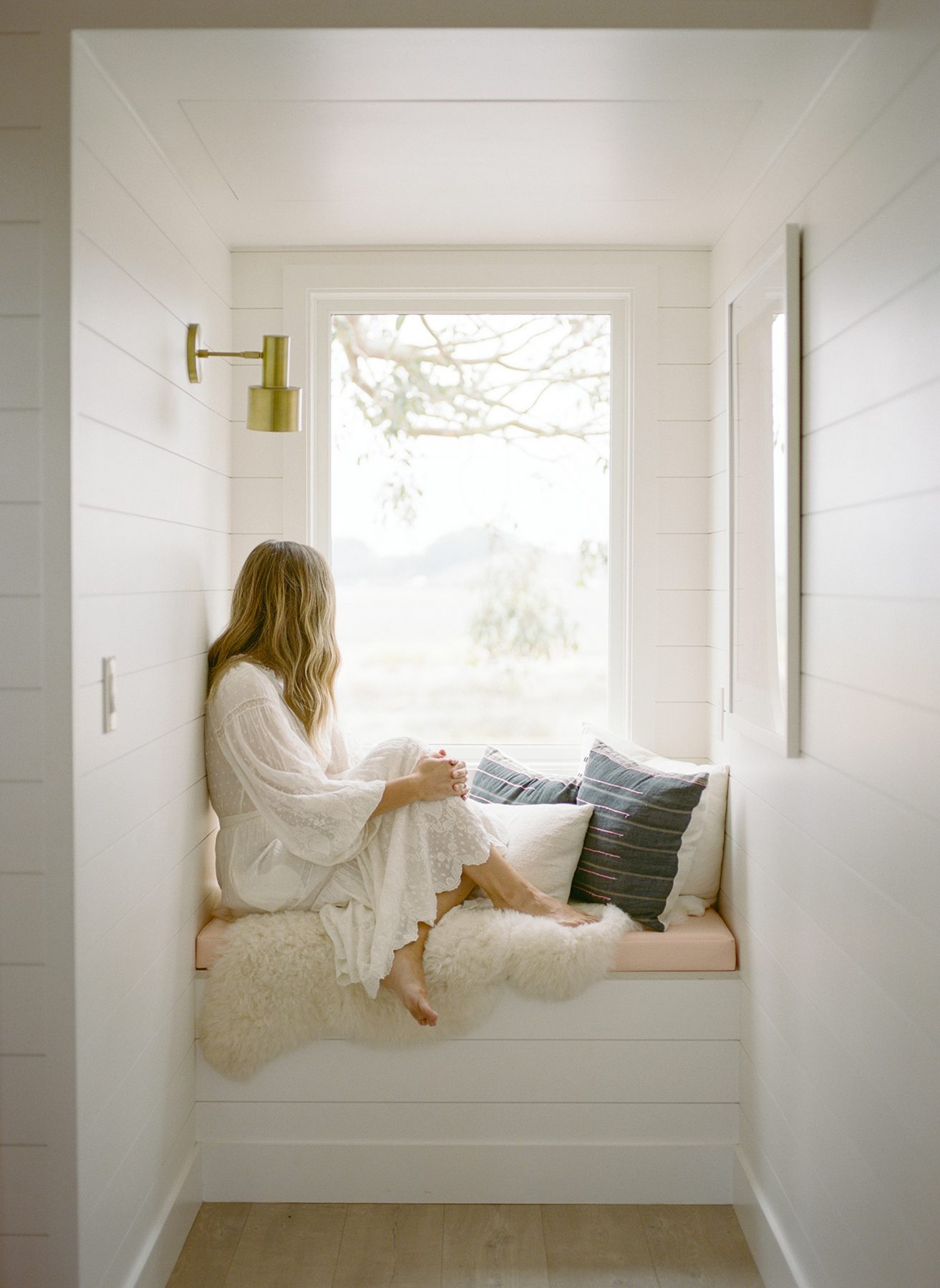Lady sitting on a window seat looking out the window